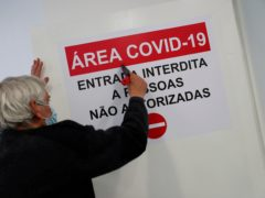 A worker puts up a sign on the door of a new Covid-19 ward being set up at the Military Hospital in Lisbon (Armando Franca/AP)