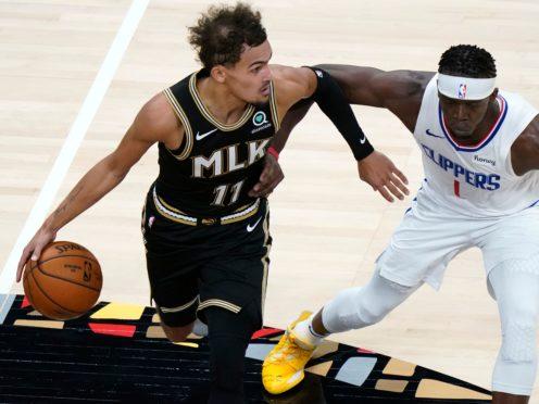 Atlanta Hawks guard Trae Young drives against Los Angeles Clippers guard Reggie Jackson (John Bazemore/AP)