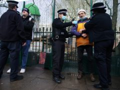 Police officers detain a man at the encampment in Euston Square Gardens (Aaron Chown/PA)