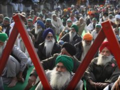 Indian farmers listen to their leader Rakesh Tikait at the Delhi-Uttar Pradesh border, in New Delhi (AP)