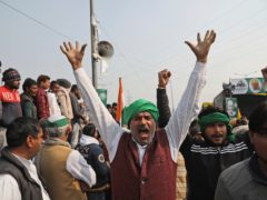 Farmers shout slogans as they arrive at the site of an ongoing protests against farm laws at the Delhi-Uttar Pradesh border, on the outskirts of New Delhi, India, Friday, Jan. 29, 2021. Major Indian opposition parties boycotted the opening day of Parliament's budget session Friday in solidarity with farmers engaged in a 2-month standoff over new agricultural laws the government refuses to repeal. The protests were marked by violence on Tuesday, India's Republic Day, when tens of thousands of farmers riding tractors and on foot stormed the 17th century Red Fort in a brief but shocking takeover that played out live on news channels. (AP Photo/Manish Swarup)