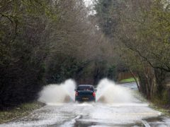 A car drives through floodwater near Dorcester-on-Thames, Oxfordshire (Steve Parsons/PA)