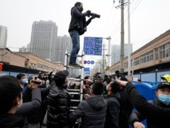 A photographer on a ladder tries to take photos of the World Health Organisation convoy after it entered Huanan Seafood Market on the third day of a field visit in Wuhan in central China's Hubei province (Ng Han Guan/AP)