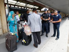 Police officers check identity documents at Saint-Charles railway station in Marseille, southern France (Claude Paris/AP)