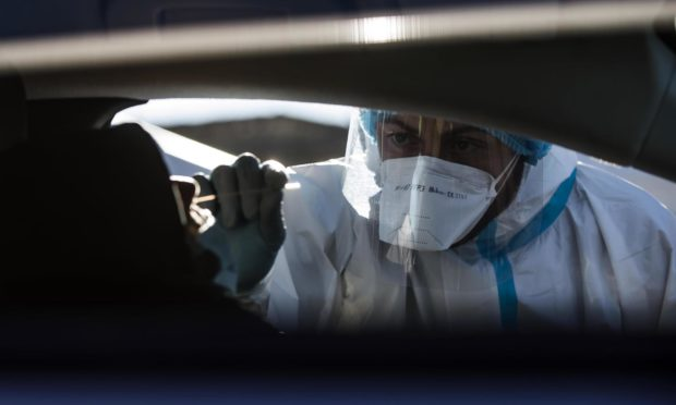 Mandatory Credit: Photo by ANGELO CARCONI/EPA-EFE/Shutterstock (11714812a) A health worker wearing overalls, a protective mask and a face visor performs swab tests on motorists