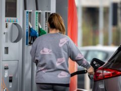A woman at GO Petrol Station in Belfast, where the owners have displayed a sign notifying customers that the pumps are disinfected regularly to combat Covid-19, after Prime Minister Boris Johnson has put the UK in lockdown to help curb the spread of the coronavirus.