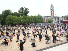 People take a knee during a Black Lives Matter protest rally at Windrush Square, Brixton, south, London, in memory of George Floyd (Yui Mok/PA)