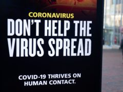 A person passes a 'Don't help the virus spread' government coronavirus sign in Bournemouth (Andrew Matthews/PA)