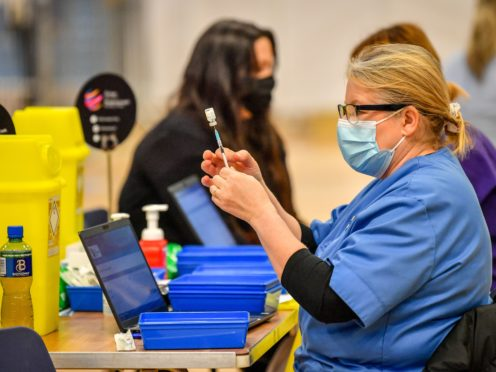 Health care workers give out injections of the Pfizer vaccine at a coronavirus vaccination centre set up at Cwmbran Stadium (Ben Birchall/PA)