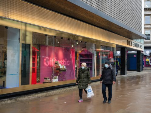 Two people wearing face masks pass the closed Debenhams flagship store on Oxford Street in central London (Dominic Lipinski/PA)