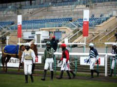 Jockeys wearing facemasks at Doncaster with empty stands behind them – horse racing in Covid times (PA)
