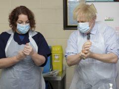Prime Minister Boris Johnson is shown how to prepare the vaccine (Jon Super/PA)