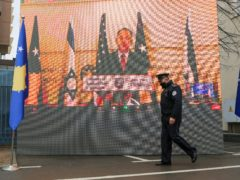 A Kosovo police officer in Pristina walks by a screen displaying a virtual signing ceremony address by Israeli foreign minister Gabriel Ashkenazi (Visar Kryeziu/AP)