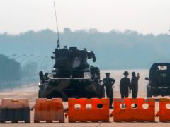 Myanmar's military stand guard at a checkpoint manned with an armored vehicle in a road leading to the parliament building on Tuesday in Naypyitaw (AP)
