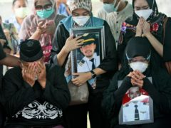 Relatives weep as they pray during the burial of Fadly Satrianto, a victim of the crash of Sriwijaya Air flight SJ-182 in Surabaya, East Java (AP)
