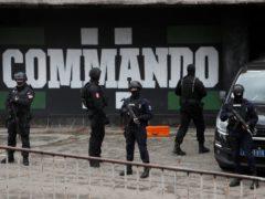 Serbian police officers guard Partizan stadium during a raid in Belgrade (Darko Vojinovic/AP)