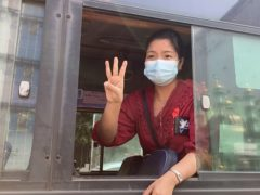A woman flashes the three-fingered salute from a vehicle as a crowd of protesters march past in Yangon (AP)