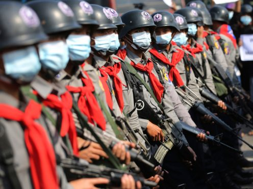 Armed riot police are seen near protesters in Naypyitaw, Myanmar (AP)