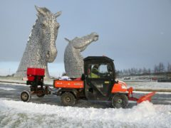 A staff member uses a vehicle to clear snow on a pathway at the Kelpies near Falkirk in Scotland (Andrew Milligan/PA)