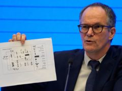 Dr Peter Ben Embarek holds up a chart showing pathways of transmission of the virus during a press conference held at the end of the WHO mission in Wuhan, China (Ng Han Guan/AP)