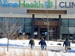 Police walk towards the Allina Health clinic (David Joles/AP)