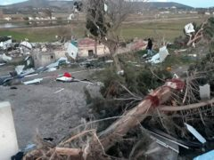 A man walks among the debris after a small tornado has struck Cesme, a town on Turkey's Aegean coast, leaving a path of destruction and injuring sixteen people, Friday, Feb. 12, 2021, officials and reports said Friday. The tornado touched down late on Thursday in the resort town of Cesme, some 90 kilometers (56 miles) west of the city of Izmir, where it uprooted trees, blew off roof tiles, swept up cars and knocked down a crane. (IHA via AP)