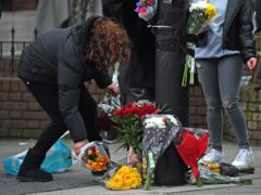 A woman lays a floral tribute on Ackmar Road near Parsons Green Tube station (Kirsty O'Connor/PA)