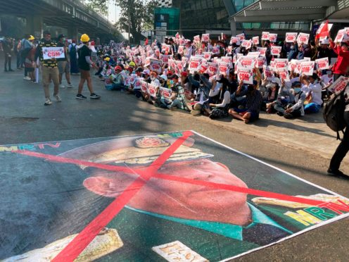 A large image that has an X mark on the face of Senior General Min Aung Hlaing lies on the road as anti-coup protesters gather in Yangon, Myanmar (AP)