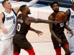 Portland Trail Blazers guard Damian Lillard goes for a lay-up in front of Dallas Mavericks centre Kristaps Porzingis (Michael Ainsworth/AP)