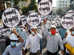 Engineers hold placards with Burmese signs about civil disobedience as they hold an anti-coup protest march in Mandalay (AP)