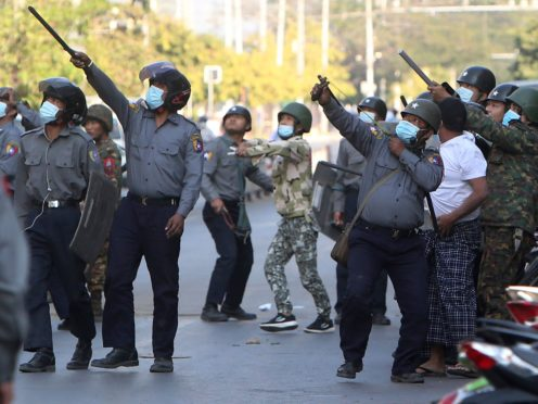 A policeman aims a catapult towards an unknown target during a crackdown on anti-coup protesters holding a rally in front of the Myanmar Economic Bank in Mandalay (AP)