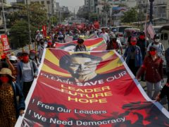 Demonstrators display pictures of detained Myanmar leader Aung San Suu Kyi (AP)