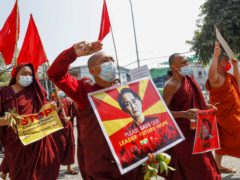 Buddhist monks and nuns display pictures of detained Myanmar leader Aung San Suu Kyi during a protest against the military coup in Mandalay (AP)