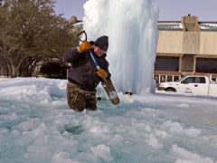 A worker breaks ice on a frozen fountain in Richardson, Texas (LM Otero/AP)