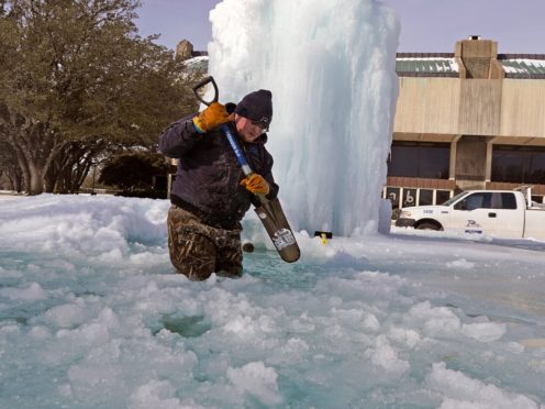 A worker breaks ice on a frozen fountain in Richardson, Texas (LM Otero/AP)