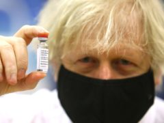 Prime Minister Boris Johnson holding a vial of the Oxford/Astra Zeneca Covid-19 vaccine as he visits a vaccination centre at Cwmbran Stadium in Cwmbran, south Wales (Geoff Caddick/PA)