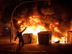 A demonstrator throws a stone during clashes with police in Barcelona (AP)