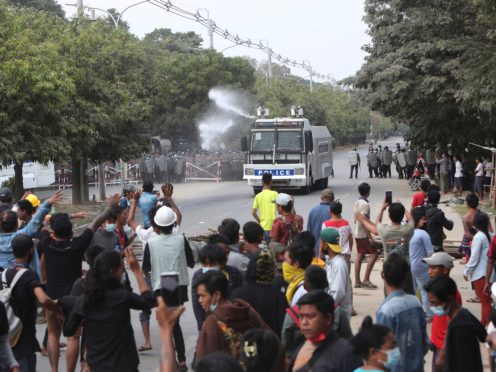 A police truck uses a water cannon to disperse protesters in Mandalay, Myanmar (AP)