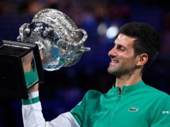 Novak Djokovic holds the Norman Brookes Challenge Cup aloft (Andy Brownbill/AP)
