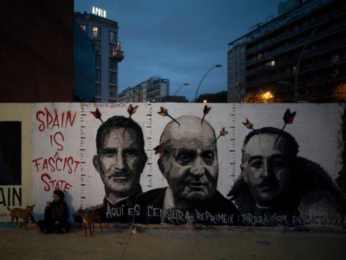 Graffiti depicting Spain's King Felipe VI, former King Juan Carlos and Spain's late dictator Francisco Franco by artist BlackBlock, in support of Catalan rap artist Pablo Hasel (Felipe Dana/AP)