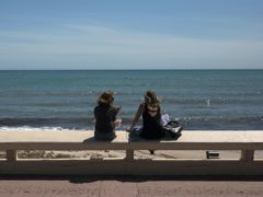 Two women sit above a deserted beach in Cannes (AP)