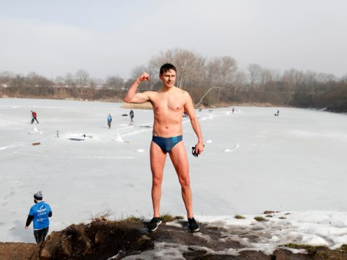 Freediver David Vencl reacts after setting a new world record in men's swimming under ice near Teplice, Czech Republic, Tuesday, Feb. 23, 2021. Vencl swam the longest distance of 80.9 meters (265 ft) on Tuesday with breath held only in his swimsuit and swim goggles. In this category, freedivers cannot use any fin, diving suit, cap and weights. (AP Photo/Petr David Josek)
