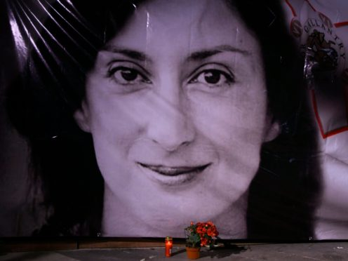 FILE – In this Tuesday, Oct. 16, 2018 file photo, flowers and a candle lie in front of a portrait of slain investigative journalist Daphne Caruana Galizia during a vigil outside the law courts in Valletta, Malta. One of three men accused of killing Maltese investigative journalist Daphne Caruana Galizia in a 2017 car bombing changed his plea to guilty during a hearing Tuesday and was immediately sentenced to 15 years in prison. The man, Vince Muscat, together with Alfred and George Degiorgio, had been accused of detonating the bomb that killed Caruana Galizia as she was driving her car Oct. 16, 2017. (AP Photo/Jonathan Borg, File)