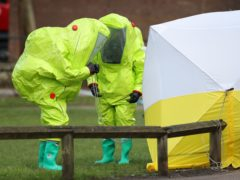 Personnel in hazmat suits working to secure a tent covering a bench in the Maltings shopping centre in Salisbury (Andrew Matthews/PA)