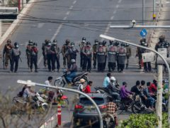 Police stand in formation blocking a main road in Mandalay (AP)