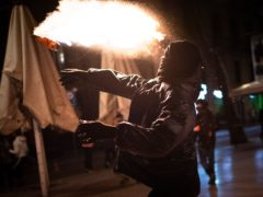 A protestor throws a molotov cocktail during clashes in Barcelona (AP/Emilio Morenatti)