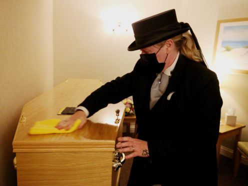 Funeral director Colette Sworn polishes the lid of a coffin as part of her preparations to oversee a funeral in the chapel at Co-op Funeralcare in Watford, Hertfordshire (Jonathan Brady/PA)