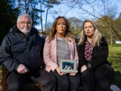 Lisa Dorrian's father John and her sisters Michelle (centre) and Joanne (right) sitting a memorial bench to Lisa at Castle Park in Bangor beside a cherry blossom tree planted by her friends 16 years ago (Liam McBurney/PA)