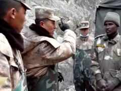 In this image taken from video footage run Feb. 19, 2021 by China's CCTV via AP Video, China's People's Liberation Army (PLA) regimental commander Qi Fabao, second from left, talks with members of the Indian military as Indian and Chinese troops face off in the Galwan Valley on the disputed border between China and India, June 15, 2020. China's military said Friday, Feb. 19, 2021 that four of its soldiers were killed in a high-mountain border clash with Indian forces last year, the first time Beijing has publicly conceded its side suffered casualties in the deadliest incident between the Asian giants in nearly 45 years. (CCTV via AP Video)