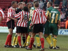 Referee Eddie Wolstenholme is caught in the middle of a melee (PA)